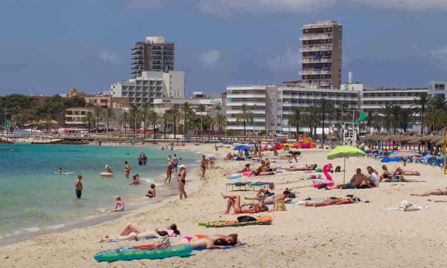 Sunbathers at Magaluf Beach on the island of Mallorca. A Mallorca outbreak has infected at least 1,176 people and left 4,796 in quarantine across Spain.