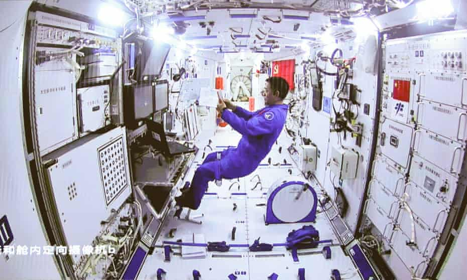 A man in a blue suit floats inside a space station module