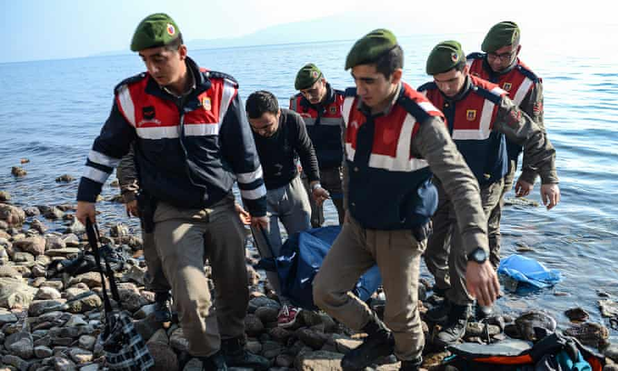 Turkish gendarmes carry the body of a migrant on a beach yesterday after at least 33 migrants drowned when their boat sank in the Aegean Sea while trying to cross from Turkey to Greece