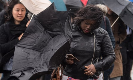 People struggling with umbrellas in high winds