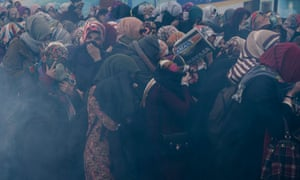 Women cower from tear gas while protesting about the government takeover of Zaman in Istanbul.