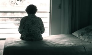 An older woman sits on a bed looking out a window