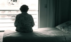 An elderly woman sits alone in a bedroom