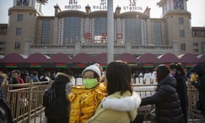 A woman holds a child wearing a face mask outside the Beijing Railway Station on Tuesday.