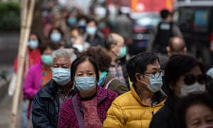 People line up to receive free face masks in Hong Kong.