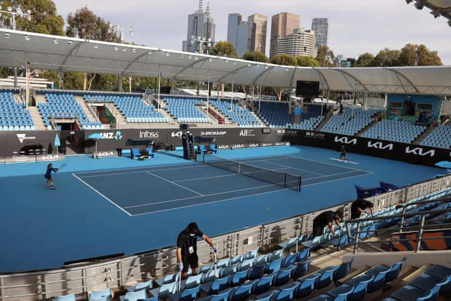 Workers clean the seats on court 3 during a warm up session at the Melbourne Park ahead of the Australian Open.