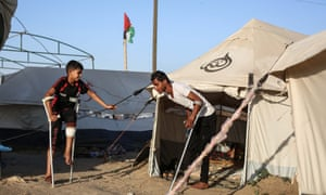 Palestinians on crutches at al-Bureij refugee camp on 17 May.