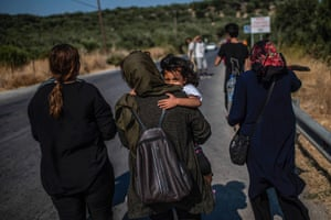 A migrant woman carries a little girl as they walk outside the official refugee camp of Moria.