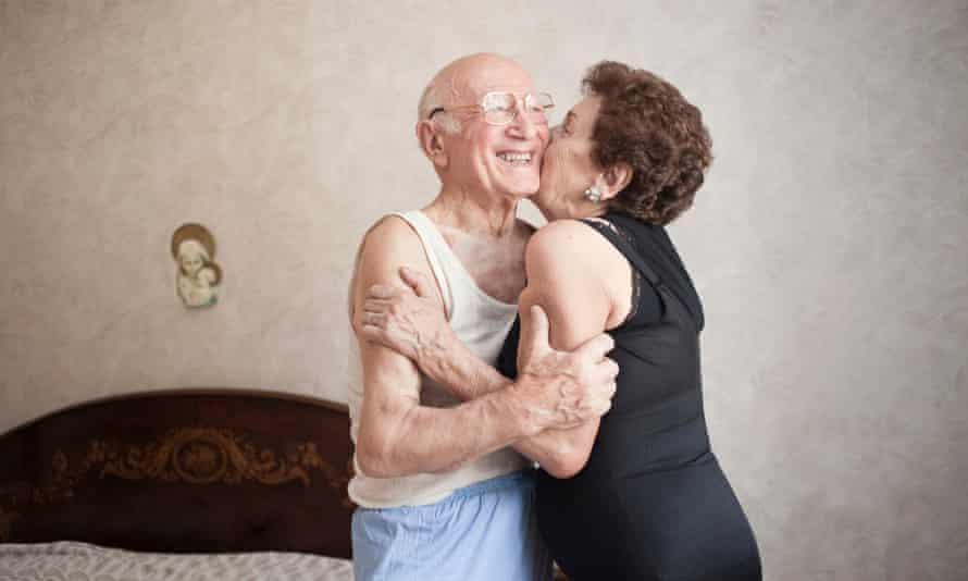 Happy older couple hugging in a bedroom