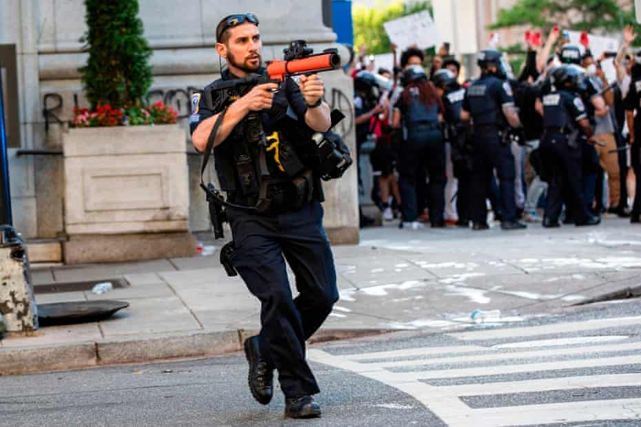 A police officer aims a non-lethal launcher at protesters as they clash in Washington DC on 31 May.