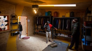 Refugees try on clothes in the men's clothing store at the Katsikas refugee camp in Greece