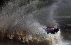 The Peugeot of Sebastien Loeb and Daniel Elena emerges from the water.
