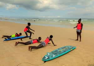 Khadjou Sambe, 25, Senegal's first female professional surfer, trains beginners with Black Girls Surf (BGS) on the sand at Yoff beach, in Dakar