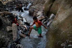 Mauricio, a 10-year-old boy, wades through the contaminated sewage water