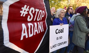 Protesters in Canberra hold banners against Adani