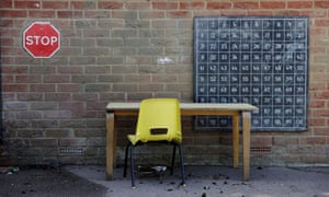 Desk and chair against a wall outside