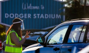 Stephanie Campos, left, confirms COVID-19 test appointment notification on patients' phones before they enter the testing site at Dodger Stadium in Los Angeles.