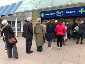 People queue outside a Boots pharmacy store in west London where stocks of hand sanitiser are limited to two per person.