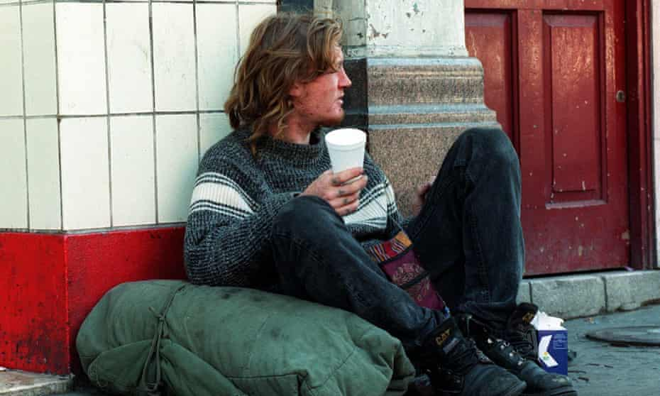 homeless man sitting beside a doorway in Camden, north London