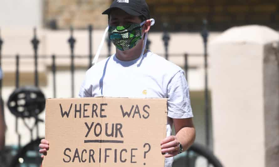 A masked protester outside Dominic Cummings's home holding a placard saying 'Where was your sacrifice?'