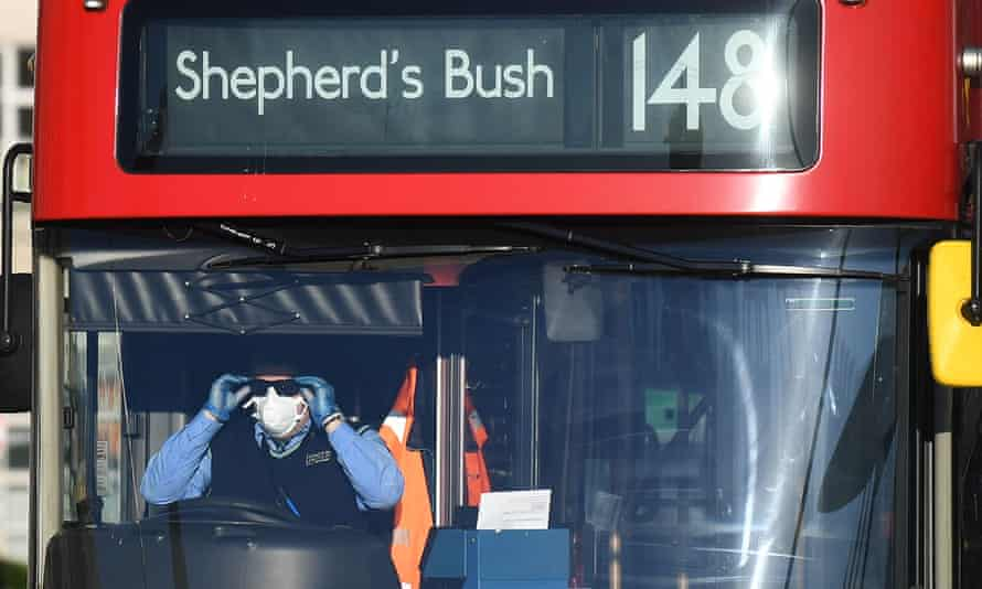 A London bus driver wearing a mask behind the wheel
