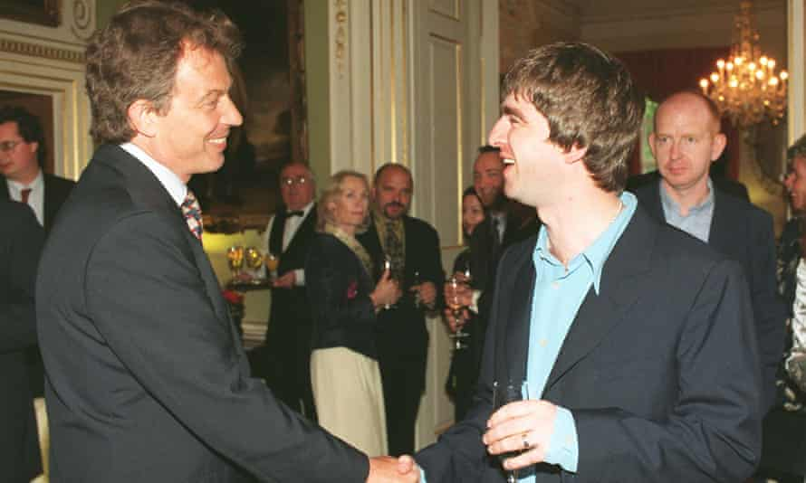 Tony Blair meets Noel Gallagher in 1997, watched by Alan McGee of Creation Records, far right.