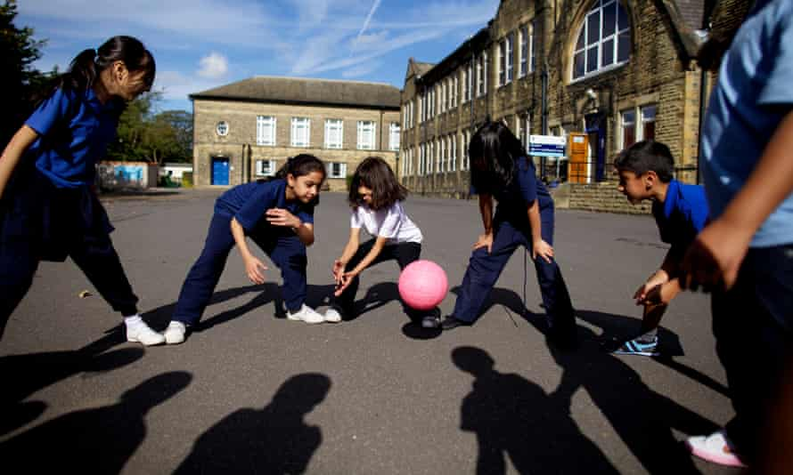 Children play with a ball in a school playground