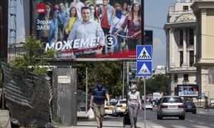 A couple wearing face masks to protect against coronavirus, walk under an electoral poster of the leader of the ruling Social Democrats Zoran Zaev, in a street in Skopje, North Macedonia on Saturday,