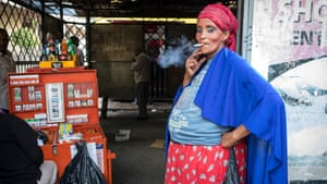 A woman stands at a smoking zone in Nairobi, Kenya. Smoking openly on the street can incur a hefty fine.