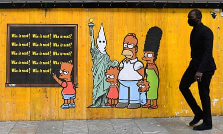"""A man walks past """"Just Because I Am Black"""", an artwork in Milan by Italian pop artist and activist aleXsandro Palombo as a tribute following the death of George Floyd and amid a widespread reckoning for US pop culture about racism."""