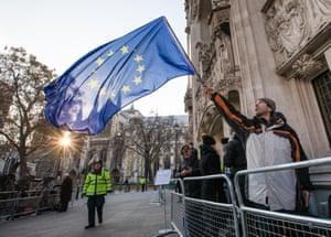 A man waves the EU flag as he waits to enter the Supreme Court in Westminster, London