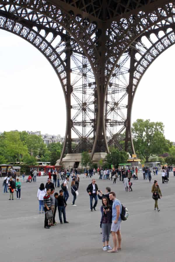 Tourists wander under the Eiffel Tower in Paris.