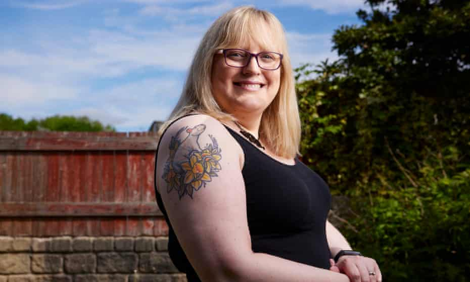 Smiling woman in glasses shows her right shoulder with a tattoo of a white rat surrounded by daffodils.