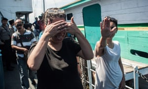 Asylum seekers cover their faces as they leave a boat in Bali, Indonesia, in 2013.