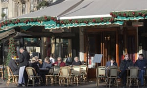 People enjoy the sun at a cafe terrace in Paris before Christmas