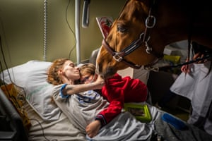 Marion 24, who has metastatic cancer, embraces her son Ethan, seven in the presence of Peyo, a therapy horse