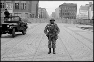 """West Berlin, west Germany 1965. American soldiers stand guard as Communist East Berlin puts up the wall.In 1962, white photojournalist Leonard Freed was on assignment in Berlin. He photographed an African-American soldier standing in front of the wall. The irony of this soldier defending the USA on foreign soil while African-Americans at home were fighting for their civil rights resonated with Freed. """"""""""""""""""""''''""""We, he and I, two Americans. We meet silently and part silently. Between us, impregnable and as deadly as the wall behind him, is another wall. It is there on the trolley tracks, it crawls along the cobble stones, across frontiers and oceans, reaching back home, back into our lives and deep into our hearts: dividing us, whenever we meet. I am white and he i""""""""""""""""""""""""""""s Black."""""""