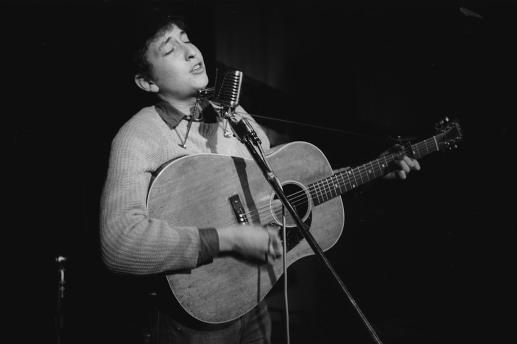 Dylan performs onstage that same night (Note: at Gerde's Folk City). Photograph Copyright: Ted Russell