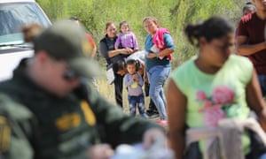 Central American asylum seekers wait as US border patrol agents take them into custody on 12 June 2018 near McAllen, Texas.
