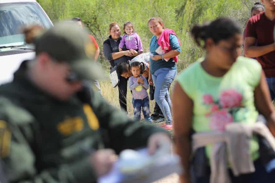 US border patrol agents take people into custody near the border.