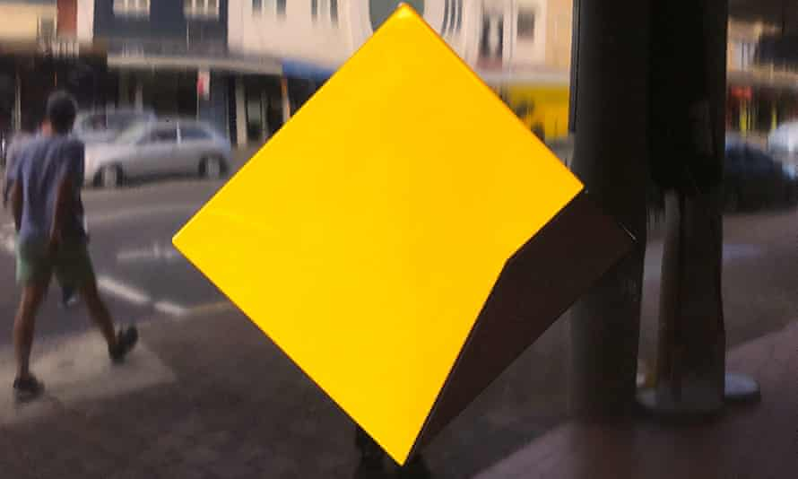 A pedestrian walks past a logo for the Commonwealth Bank outside a branch in Sydney