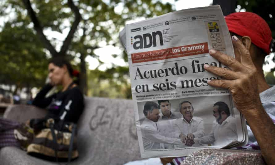 A man in Cali, Colombia, reads a newspaper with a front-page headline reading 'Final agreement in six months' following the deal between the government and Farc rebels in Cuba.