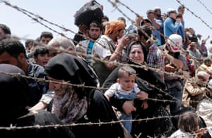 Refugees seen through barbed wire as they wait on the Syrian side of the border crossing near Akçakale