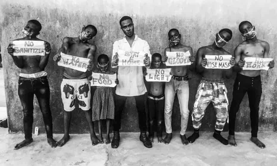 Children hold signs outside Sari market in Orile-Iganmu, Lagos state