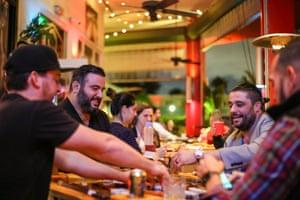Chef José Mendín and Maximo Silva play dominoes at La Placita, Mendín's restaurant in Miami.