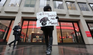 Kadijah Amen-Rah takes part in the counter-protest on a mostly empty sidewalk in front of the NFL's headquarters.