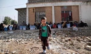 A handout picture released by Save The Children shows Ali, a five-year-old displaced Iraqi boy playing as he waits to be screened at a checkpoint north-west of Kirkuk, after his family fled the Islamic State-held Hawija area