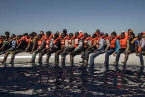 Migrants from Eritrea, Mali, Bangladesh and other countries wait to be rescued, off the coast of Libya
