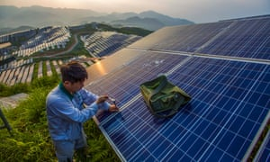 A worker maintains photo-voltaic panels