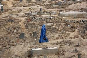 A woman walks through a cemetery in Kabul, Afghanistan